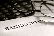 a bankruptcy notice letter with calculator and eyeglasses